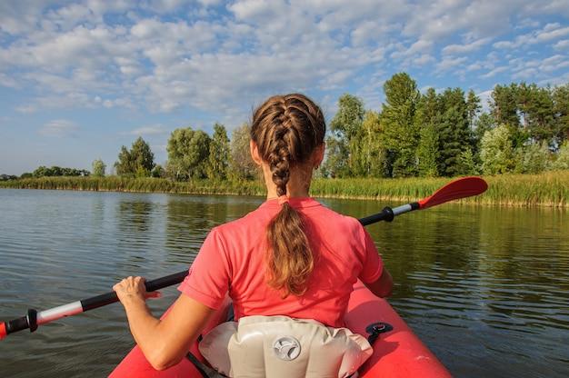 明るい服を着た女の子がウクライナの川のカヤックに浮かんでいます