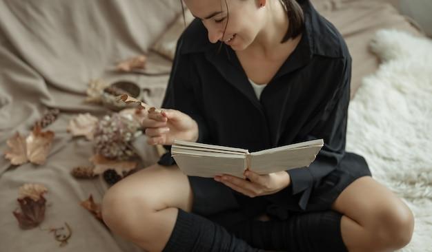 居心地の良い家庭服を着た女の子が紅葉の中で本を持ってベッドに座っています。