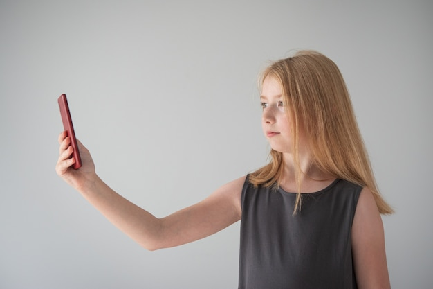 灰色のドレスを着て、灰色の背景に電話を持っている女の子が写真を撮ります
