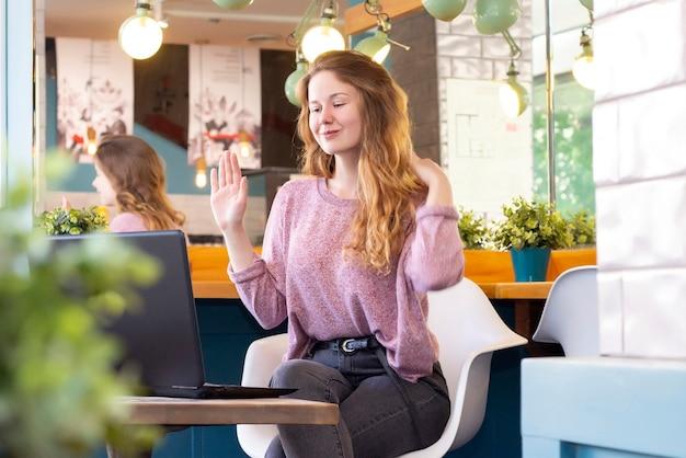 헤드폰을 쓴 소녀는 랩톱에서 화상 채팅을 통해 통신합니다. 원격 작업, 온라인. 커피 한잔과 함께 카페에서 소녀, 손을 흔들며 인사