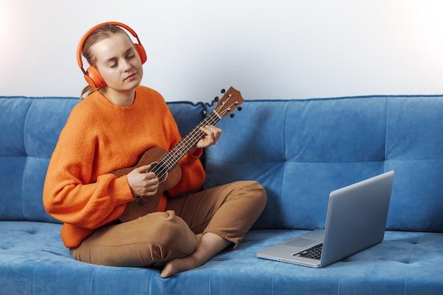 ヘッドフォンの女の子がコンピューターでウクレレを録音する
