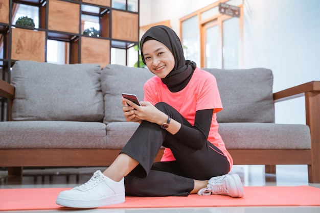 ヒジャーブのスポーツウェアの女の子が床に座って携帯電話を見て微笑む