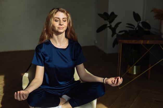 Девушка в домашней пижаме сидит дома в кресле и медитирует на солнце