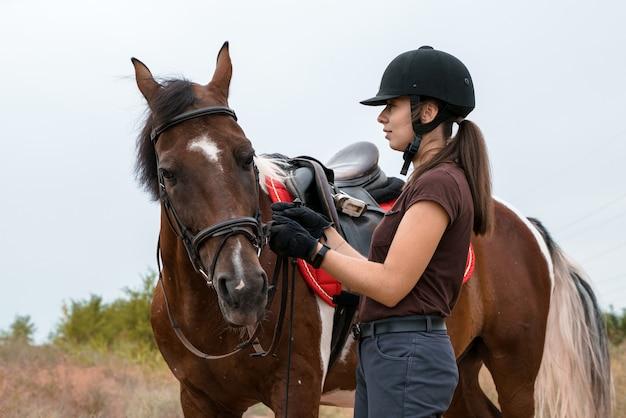 Девушка в снаряжении для верховой езды стоит на полевой дороге рядом со своей пегой лошадью и держит ее за поводья.