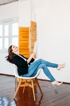ジーンズの光のジャケットの女の子は、彼女の手、ファッション、読書、エンターテイメント、職業、出版社、フリーランサー、家に雑誌を置いて椅子に座っています。