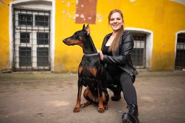 오래된 마당에서 도베르만과 함께 가죽옷을 입은 소녀. 고품질 사진