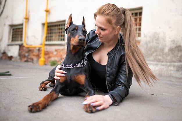 Девушка в коже с доберманом в старом дворе. фото высокого качества