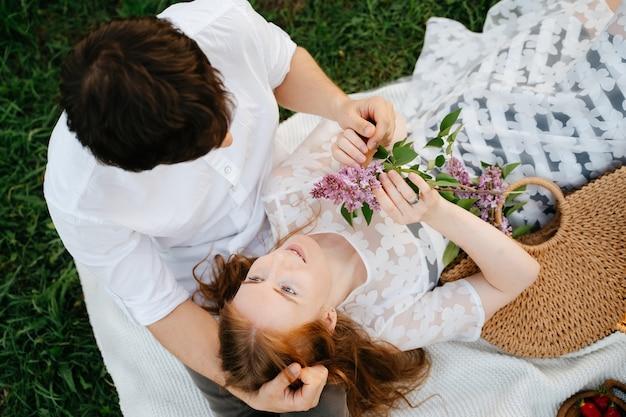 Влюбленная девушка смотрит на мужа, лежащего у него на коленях пикник семейной пары на лужайке в парке