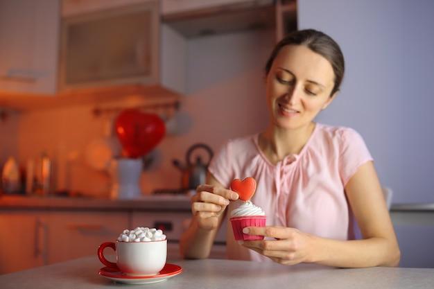Влюбленная девушка готовит кексы для любимого человека на день всех влюбленных, украшая десерт сердечком. красивое и вкусное признание в любви.