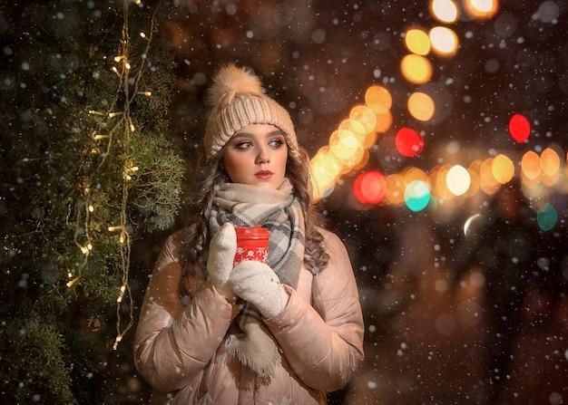 ミトンと帽子の女の子がクリスマスツリーの横にある赤いコーヒーのマグカップを保持しています。ベージュのジャケットの女の子の冬の肖像。クリスマスの肖像画。
