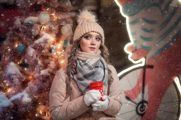ミトンとピンクのクリスマスツリーの横にある帽子の女の子。冬のベージュのジャケットでかわいい女の子の肖像画。赤いコーヒーのマグカップを持つ女性のクリスマスの肖像画。