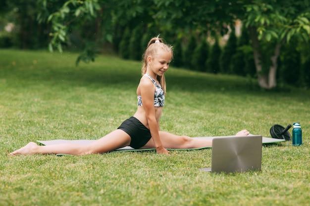 Девушка на природе возле своего дома сидит на шпагате и тренируется в сети