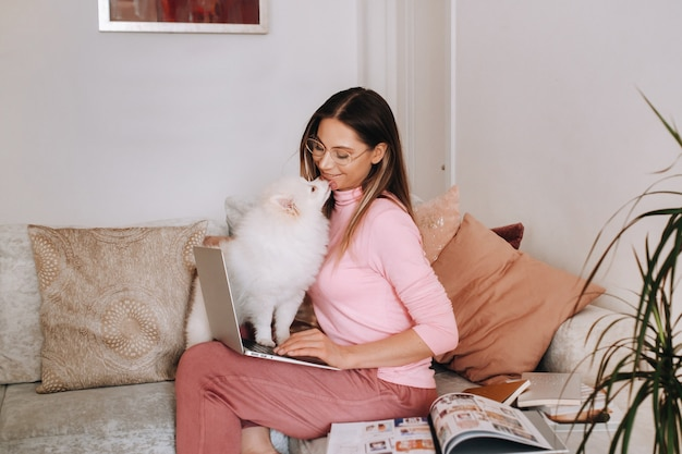 自宅でパジャマを着た女の子が犬のスピッツァーと一緒にノートパソコンで作業しており、犬とその飼い主はソファで休んでノートパソコンを見ています。家事。
