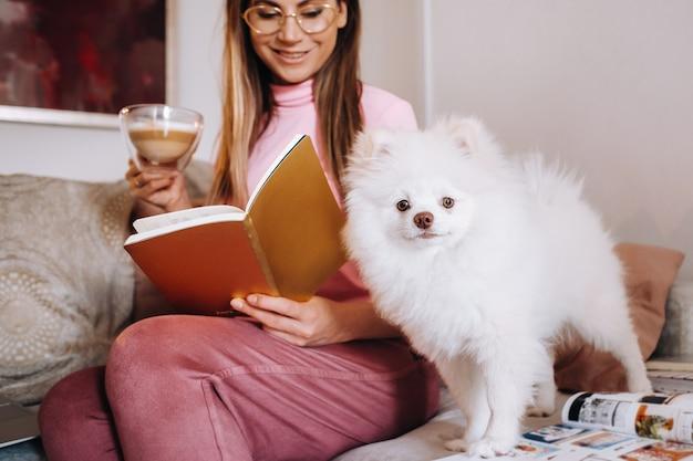 Девушка в пижаме дома читает книгу со своей собакой спитцером, собака и ее хозяйка отдыхают на диване и читают книгу. домашние дела.