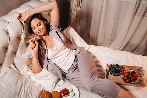 Девушка в пижаме лежит ночью в постели и ест клубнику, девушка в постели ест сладкое перед сном.