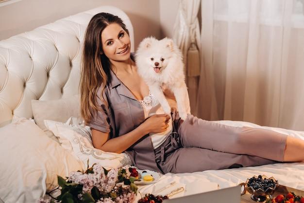 パジャマ姿の女の子が夜、白い犬と一緒にノートパソコンを見てお菓子を食べながらベッドに座っています。自宅のベッドで犬のスピッツァーと一緒にいる女の子。