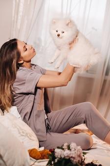 잠옷을 입은 소녀가 밤에 침대에 앉아 노트북을보고 과자를 먹고있는 하얀 강아지와 함께 침대에서 집에서 강아지 스피처를 가진 소녀.