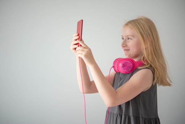 ピンクのヘッドフォンと灰色の背景に赤い電話を持つ女の子が写真を撮ります