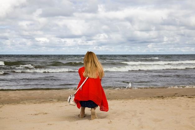 발트해 연안을 따라 걷는 붉은 옷의 소녀