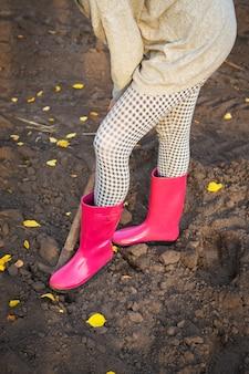 Девушка в резиновых сапогах стоит в саду с лопатой и копает. крупный план. сельское хозяйство.