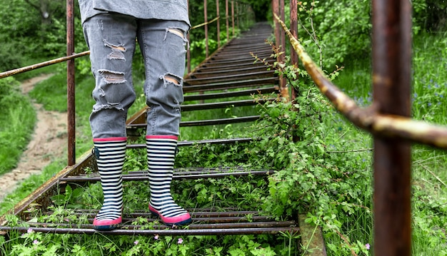 ゴム長靴の女の子が雨の春の天気で森の中を歩くクローズアップ