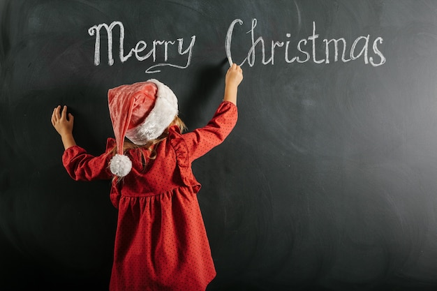 サンタクロースの帽子をかぶった少女が黒板にクリスマスの絵を描く