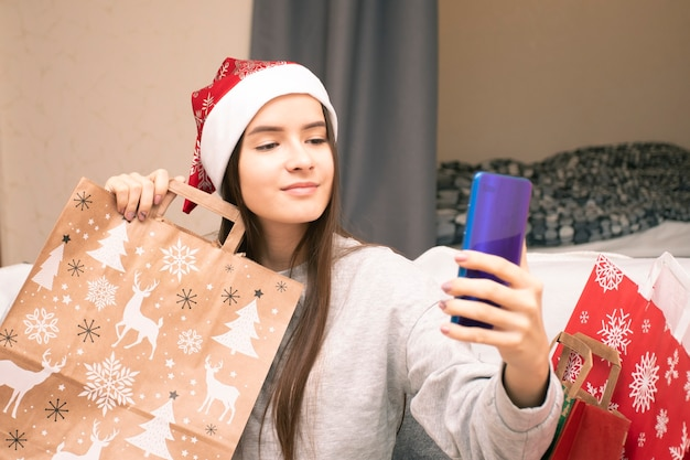 サンタの帽子をかぶった女の子が家に座っている間、ビデオリンクで友人や家族を祝福します