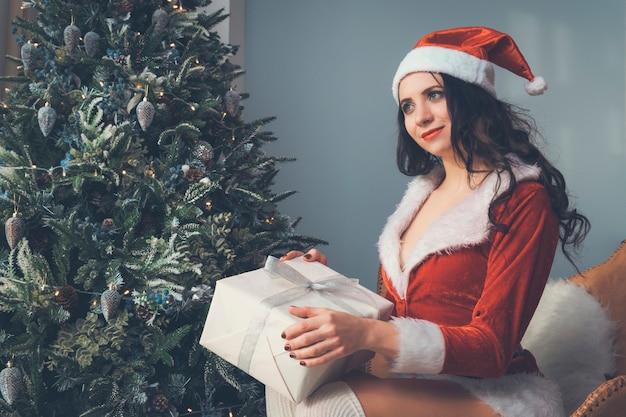 サンタの衣装を着た女の子がクリスマスプレゼントを夢見ています。クリスマスツリーの背景に贈り物を持って、奇跡を見越して窓の外を思慮深く見ている若い女性。