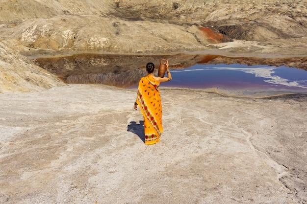 肩にピッチャーを持ったサリーの女の子が、人けのない風景の中の汚れた湖に水を求めて行きます