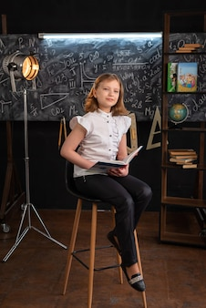 학교 옷을 입은 소녀가 손에 교과서를 들고 의자에 앉아있다.