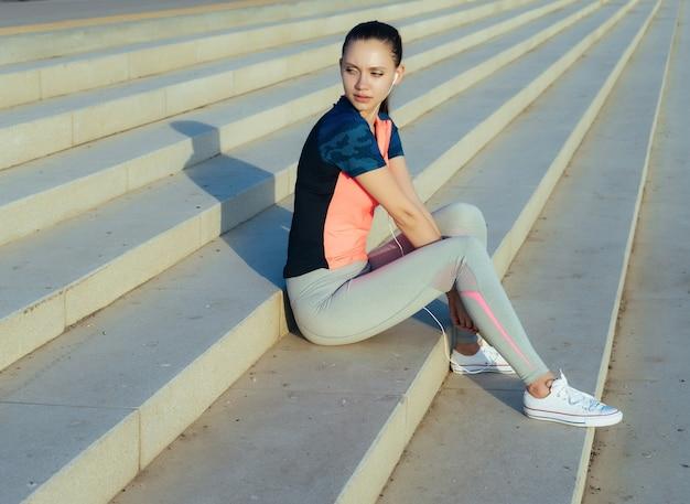 スポーツ服を着た女の子がジョギングした後、小さな女性に座っています