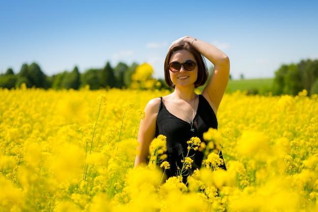 Девушка в солнечных очках улыбается летом в желтом поле