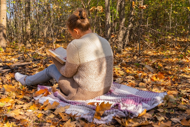 森の中の女の子が本を読んでいます。森の中で休む