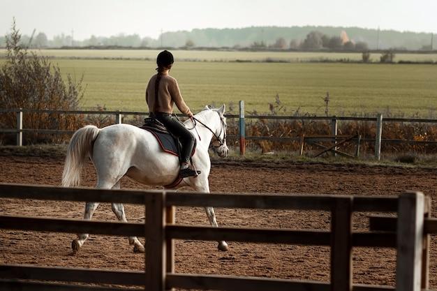 騎手の形をした女の子がヒッポドロームで馬に乗る。乗馬レッスン、乗馬。