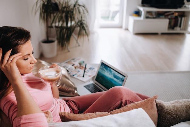 Девушка утром в пижаме дома работает на ноутбуке с питьем кофе, девушка самоизоляция дома и отдыхает на диване и смотрит на ноутбук. домашние дела.
