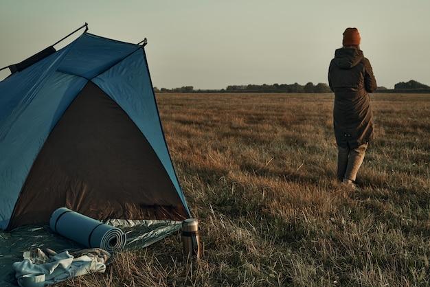 텐트 근처 공원에서 소녀가 일출, 가을 시간을 본다. 여행, 자연의 일출.