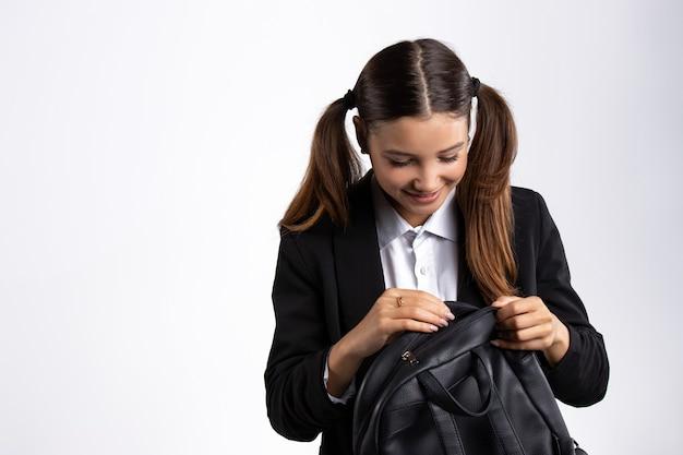 제복을 입은 소녀와 땋은 머리가 그녀의 배낭 흰 벽에서 찾고 있습니다.