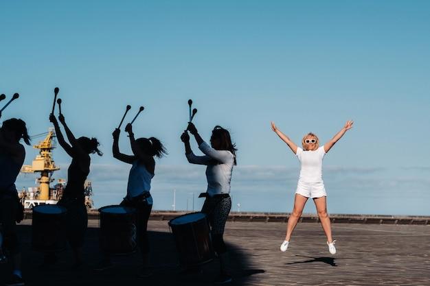 白い服を着た女の子が、ウォーターフロントのサンタクルスデテネリフェの街でフィットネスをしている人々の背景に飛びつきます。カナリア諸島、スペイン。