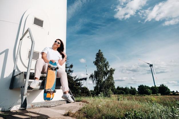スケートを手にした白い服を着た女の子が、木々のある畑の大きな風力タービンの近くで撮影されています。風車のある畑に乗るためのボードを持った現代の女性。