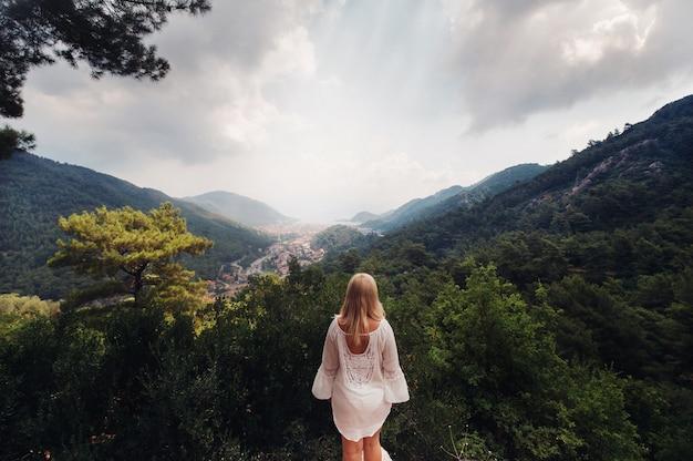Девушка в белом отстраняется и смотрит на просторы ущелья в горах, женщина в горах турции наслаждается природой.