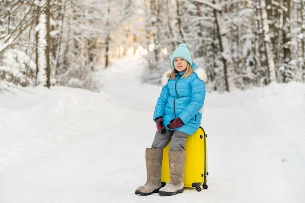 冬のフェルトブーツを履いた女の子は、凍るような雪の日にスーツケースを持って行きます。