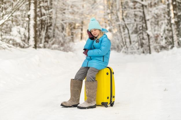 Девушка зимой в валенках сидит на чемодане в морозный снежный день