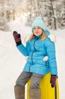 冬のフェルトブーツを履いた女の子が、凍るような雪の日にスーツケースに座っています。
