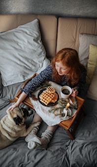 ウールの靴下を履いた女の子が、友達のパグと一緒にベッドで熱いワッフルを食べながら朝食をとります。