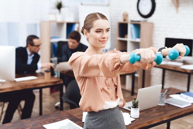 여자는 직장에서 체조 연습을하고있다.