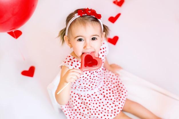 Девушка ест конфету в форме сердца. ребенок в белом платье с сердечками отмечает день влюбленных