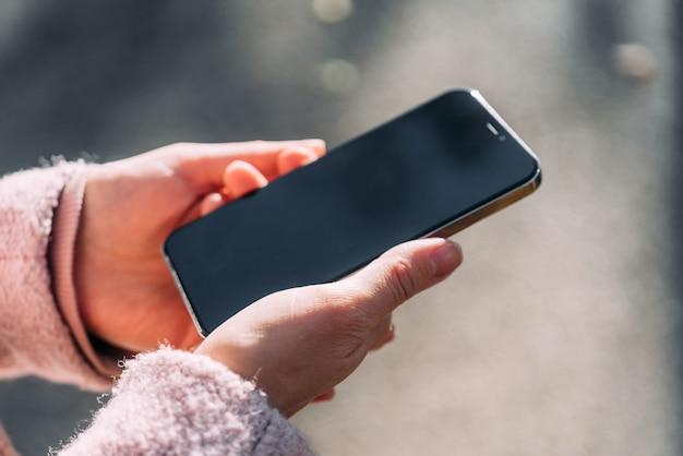Девушка держит в руках современный смартфон.