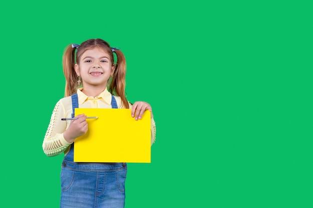 한 소녀가 팔에 연필과 노란색 교육 수업 녹색 배경의 종이를 들고 있다