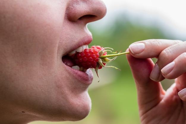 Девушка держит во рту ягодку малины