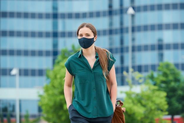 소녀는 사회적 거리를 유지하고 시내에서 보호 얼굴 마스크를 착용